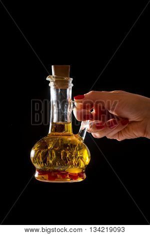 Bottle of olive oil with fresh herbs in a hend on black background.