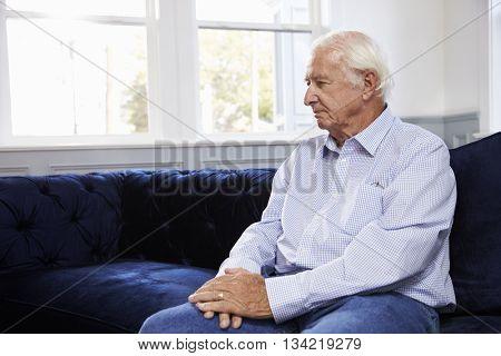 Depressed Senior Man Sitting On Sofa At Home