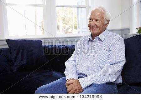 Smiling Senior Man Sitting On Sofa At Home