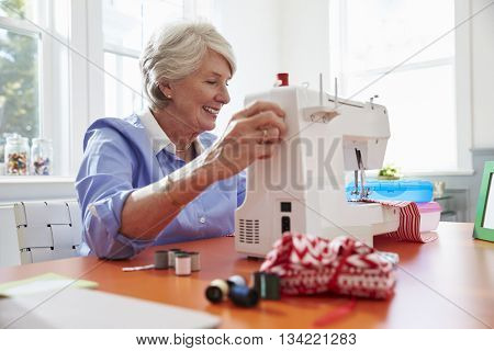 Senior Woman Making Clothes Using Sewing Machine At Home