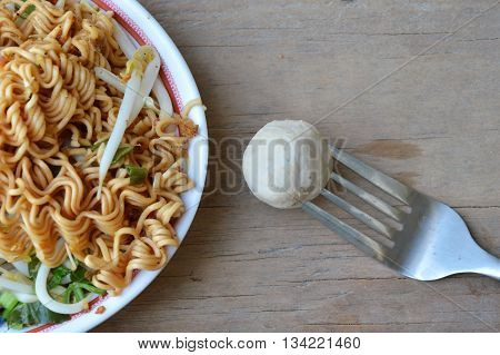 pork ball stab in fork and instant noodle boiled on dish