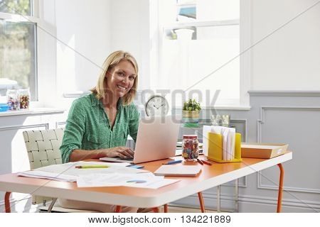 Woman Sitting At Desk Working At Laptop In Home Office