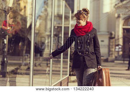 Beautiful young girl walking by a shop window carrying a suitcase