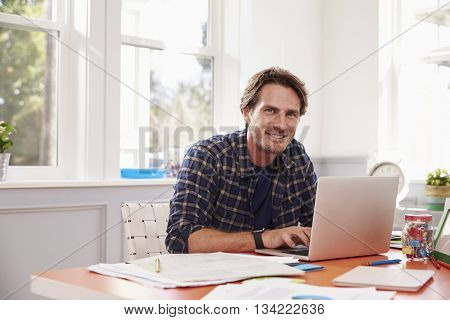 Portrait Of Man Working At Laptop In Home Office