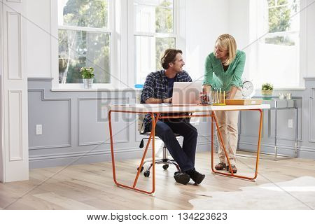 Couple Working Together At Desk In Home Office