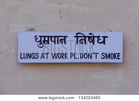 No smoking sign in English and Hindi on a wall requesting politely and humorously that nobody smokes in that public area.