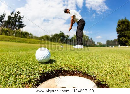 Golfer drove the ball into the hole on putting green; summer sunny day, selective focus on ball