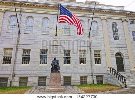 Cambridge, USA - April 29, 2015: University Hall and John Harvard Statue in the campus of Harvard University in Cambridge Massachusetts MA USA. It is a well-known monument of Harvard University founder in America.