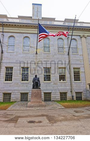 Cambridge, USA - April 29, 2015: University Hall and John Harvard Statue in the campus of Harvard University of Cambridge Massachusetts MA USA. It is a well-known monument of Harvard University founder in America.