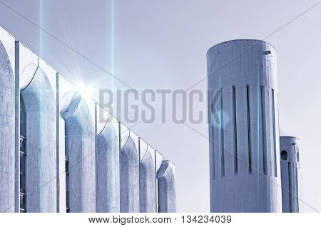 Urban architecture -concrete walls and columns built in futuristic style. Architecture monochrome modern background of architecture cityscape with stylized cosmic reflected lights over architecture.