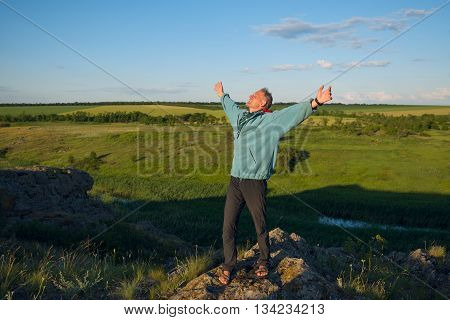 Happy hiker man stands on a cliff in the prairie his arms outstretched looking up at the sky and smiling. Sunset in a prairie desert. Azov steppes Ukraine.
