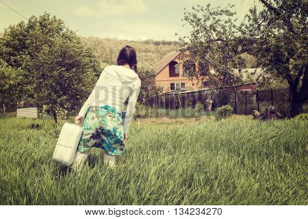 Hipster girl with vintage suitcase stands with on a green field and looks at his house before leaving. Back view. Concept - in anticipation of travel. Toned vintage image.
