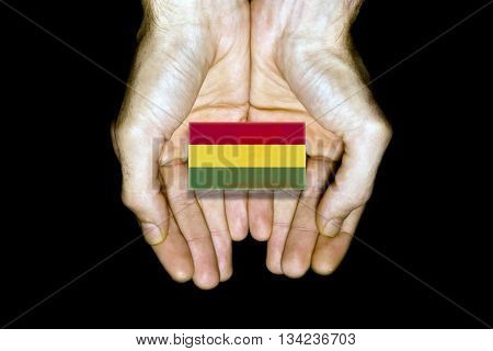 Flag of Bolivia in hands isolated on black background.
