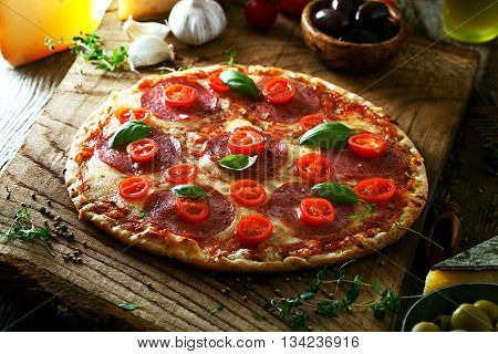 Fresh italian pizza on wood. Pizza with cheese salami and tomatoes. Fast food. Rustic pizza