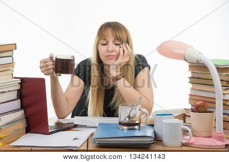 Girl Student Sadly And Sleepily Reading His Thesis Project Sitting With A Cup Of Coffee In Hand