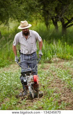 Young Farmer Weeding With A Tiller
