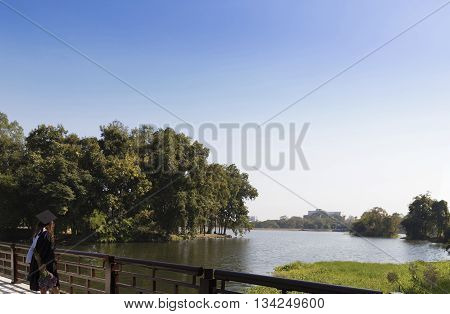 CHIANG MAI, THAILAND - JANUARY 19: woman in academic gown standing on the bridge across the pond at Chiang Mai university in Chiang Mai Thailand on January 19 2016.