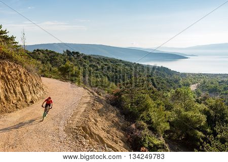 Mountain biker riding on bike at the sea and summer mountains. Man rider cycling MTB on dirt country road or single track. Sport fitness motivation inspiration in beautiful inspirational landscape.