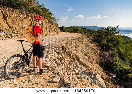 Mountain biker looking at view and riding a bike in summer woods. Man rider cycling MTB on country road or single track. Sport fitness motivation inspiration in beautiful inspirational landscape.