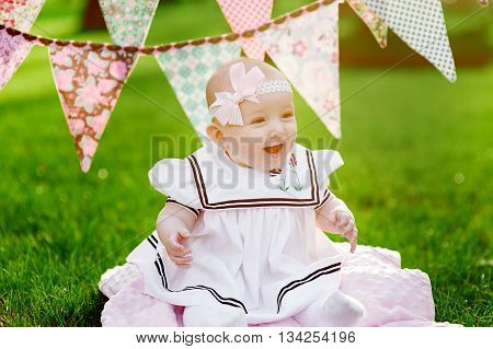 happy little girl sitting on the grass with flags on the background.