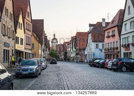 ROTHENBURG-OB-DER-TAUBER, GERMANY - JULY, 19 2015: Street view with medieval buildings, cars and unknown people walking in Rothenburg ob de Tauber, Bavaria, Germany, taken in summer, 2015.
