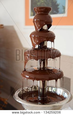 Chocolate fondue fountain with marshmallow being dipped.