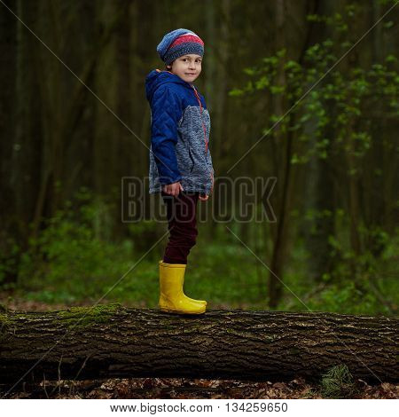 photo of little funny boy on big log
