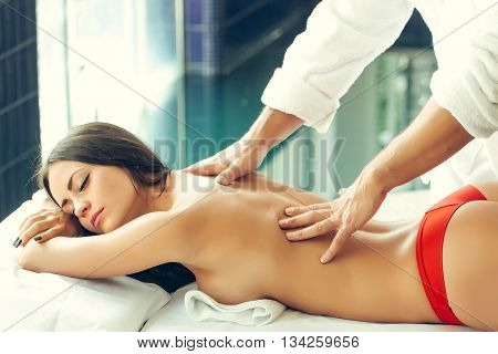 Male massage therapist in white uniform massing with hands attractive woman with sexy naked body and buttocks lying on couch