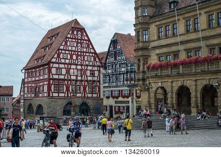 ROTHENBURG-OB-DER-TAUBER, GERMANY - JULY, 19 2015. Central square of medieval German town Rothenburg ob de Tauber with timber framing buildings and unknown peopl. Taken in Bavaria, Germany, in summer, 2015