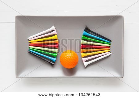 Gray ceramic dishes with golf balls and wooden tees on over white background rectangle dish