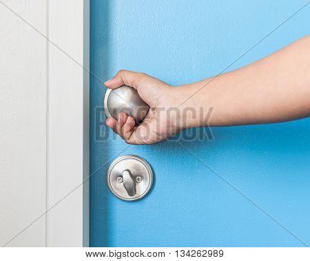 Hand Holding Metal Silver Doorknob On Wooden Door