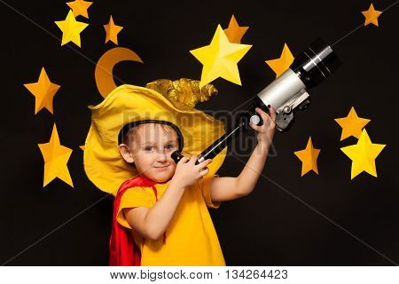 Little boy in sky watcher costume looking through a telescope among big handmade stars and moon