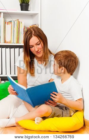 Kid boy enjoying with story telling by his mother, holding book together at their hands, sitting against bookshelf