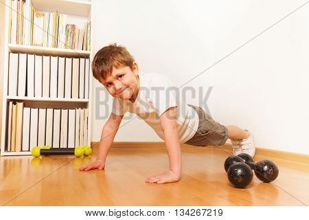 Preschooler boy working out on the floor, doing push-ups or press-ups exercises, against a white wall with copy space