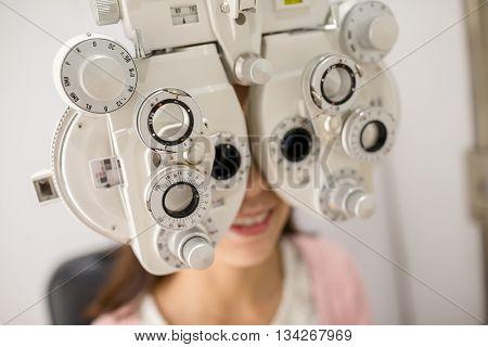 Woman looking through phoropter during eye exam