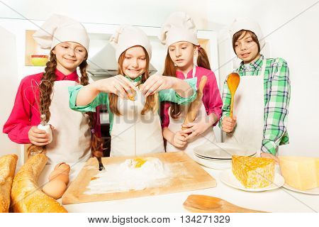 Four young cooks, boy and girls in aprons and cook's hats, learning to prepare bakery dough in the kitchen