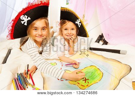 Two smiling girls wearing pirate's tricorns, drawing the map of Treasure Island with colored pencils