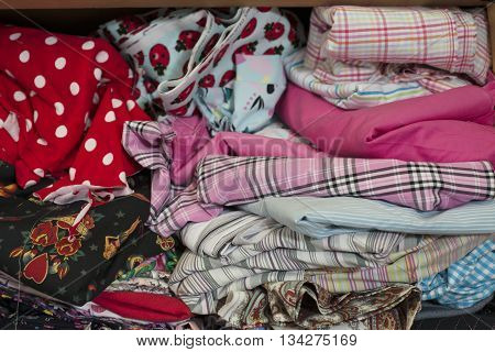 A pile of textile or cloth of various colours and designs in wooden shelving.