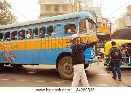 KOLKATA, INDIA - JAN 15, 2016: Policeman of road service trying to direct traffic on a street with busses and walking people on January 15, 2016. Kolkata has a density of 814.80 vehicles per km road length