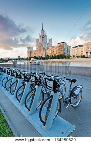 Moscow Russia - June 03 2016: Urban bike rental station in the Moscow. In the background it is a Moscow river boat and Kotelnicheskaya impressive building