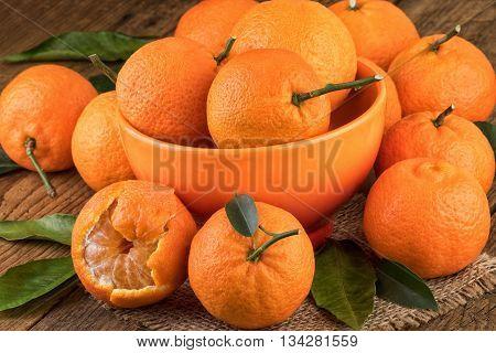 Mandarins Tangerines in orange bowl on wooden table.