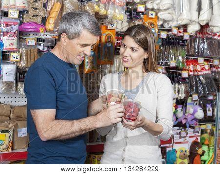 Woman Looking At Man While Choosing Pet Food In Store