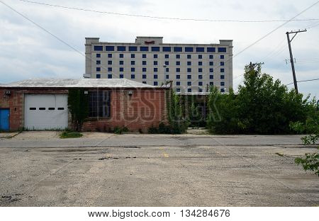 JOLIET, ILLINOIS / UNITED STATES - MAY 24, 2015: Harrah's Casino towers above an abandoned building in downtown Joliet.