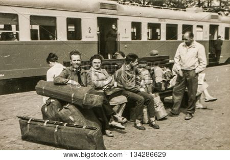LODZ, POLAND, CIRCA 1960: Vintage photo of people with big luggage waiting for a train on platform