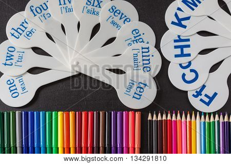 Back to school background with a lot of colorful felt-tip pens and colorful pencils and cards of numerals from one to ten with transcription and consonant letters of alphabet on the black school chalkboard