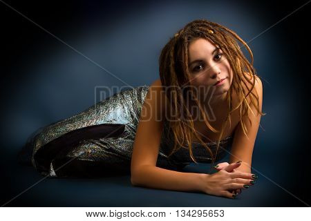 portrait of a beautiful young woman with dreadlocks against a dark background