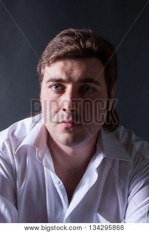 Handsome man posing in white shirt on dark background in studio.