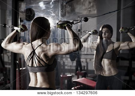 Young sexy fitness woman workout with training machine in the gym Brunette fitness woman in sport wear with perfect muscular body. Backlight and toning image