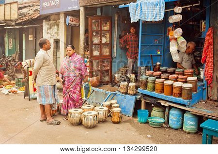 KOLKATA, INDIA - JAN 15, 2016: Elderly couple watching on musical instruments at market stall of old street on January 15, 2016. Kolkata's literacy rate of 87.14 perc. exceeds the India average of 74 perc.