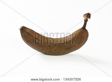 brown overripe banana on white background